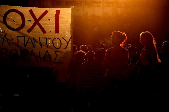 """Protesters stand next to a banner reading """" NO """" during a demonstration outside the parliament in Athens on July 22, 2015 (AFP Photo/Aris Messinis)"""
