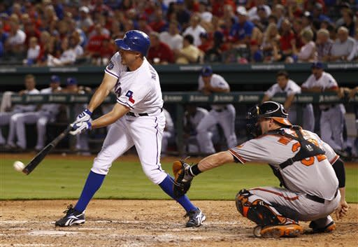 Texas Rangers' David Murphy (7) drives in a run on a single as Baltimore Orioles catcher Matt Wieters (32) looks on in the fourth inning of a baseball game, Monday, Aug. 20, 2012, in Arlington, Texas. (AP Photo/Jim Cowsert)
