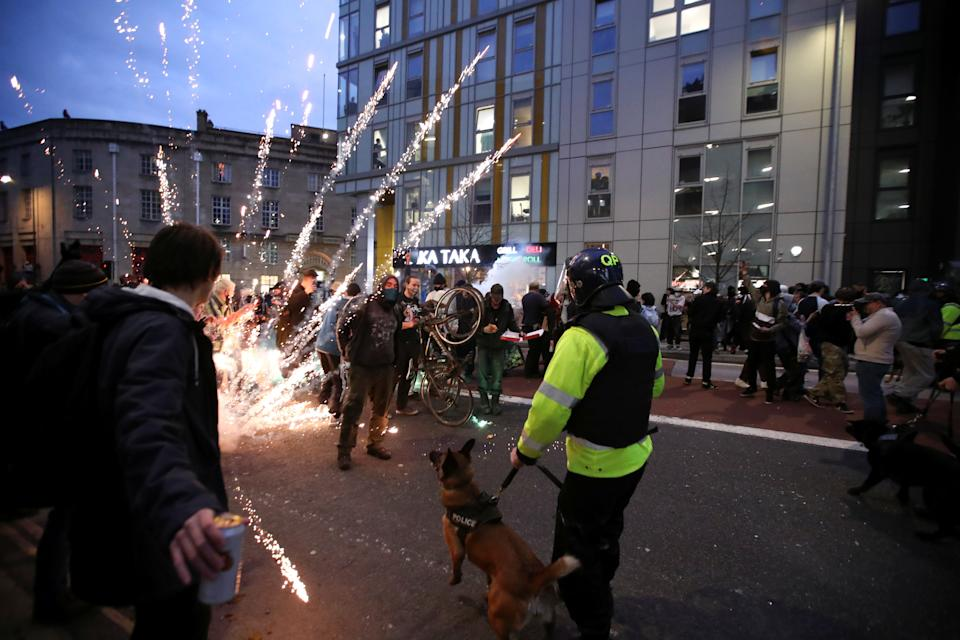 Fireworks are launched as police officers with dogs arrive to a protest against a new proposed policing bill, in Bristol, Britain, March 21, 2021. REUTERS/Peter Cziborra