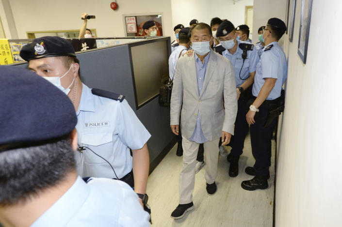 Hong Kong media tycoon Jimmy Lai, center, is escorted by police inside Apple Daily headquarters in Hong Kong Monday, Aug. 10, 2020. Hong Kong police arrested Lai and raided the publisher's headquarters Monday in the highest-profile use yet of the new national security law Beijing imposed on the city in June. (Apple Daily via AP)