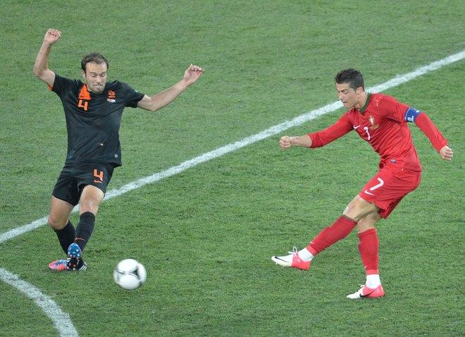 Portuguese forward Cristiano Ronaldo (R) shoots past Dutch defender Joris Mathijsen during the Euro 2012 football championships match Portugal vs. Netherlands, on June 17, 2012 at the Metalist stadium in Kharkiv.   AFP PHOTO / SERGEI SUPINSKYSERGEI SUPINSKY/AFP/GettyImages