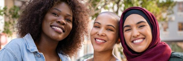 group of three women smiling, friends