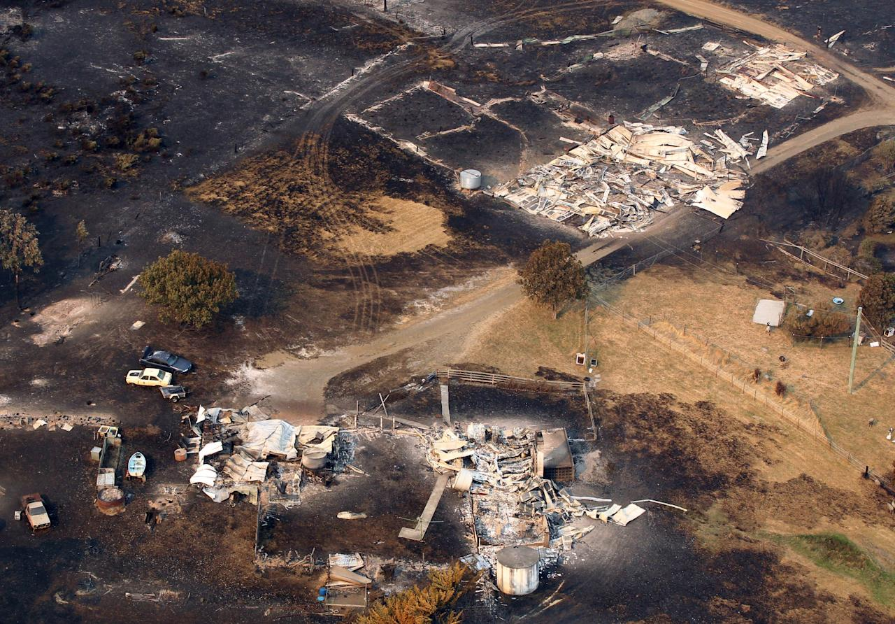 This aerial photo shows homes destroyed by a wildfire between Dunalley and Boomer Bay, east of the Tasmanian capital of Hobart, Australia, on Saturday, Jan. 5, 2013. Australian officials battled a series of wildfires amid scorching temperatures across the country on Saturday, with one blaze destroying dozens of homes in the island state of Tasmania. (AP Photo/Chris Kidd, Pool)