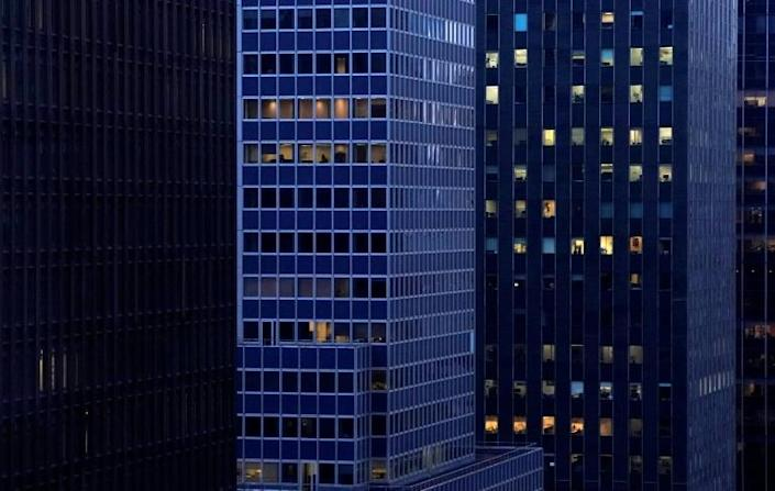 Office buildings in midtown Manhattan that used to be fully lit at sundown now show few signs of occupancy