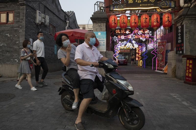 Residents wearing masks to curb the spread of the coronavirus past by lanterns and neon lights promoting a restaurant in Beijing on Friday, June 26, 2020. Even as Beijing appears to have contained the latest outbreak, businesses are still reeling from the prolonged impact of the coronavirus on the economy. (AP Photo/Ng Han Guan)