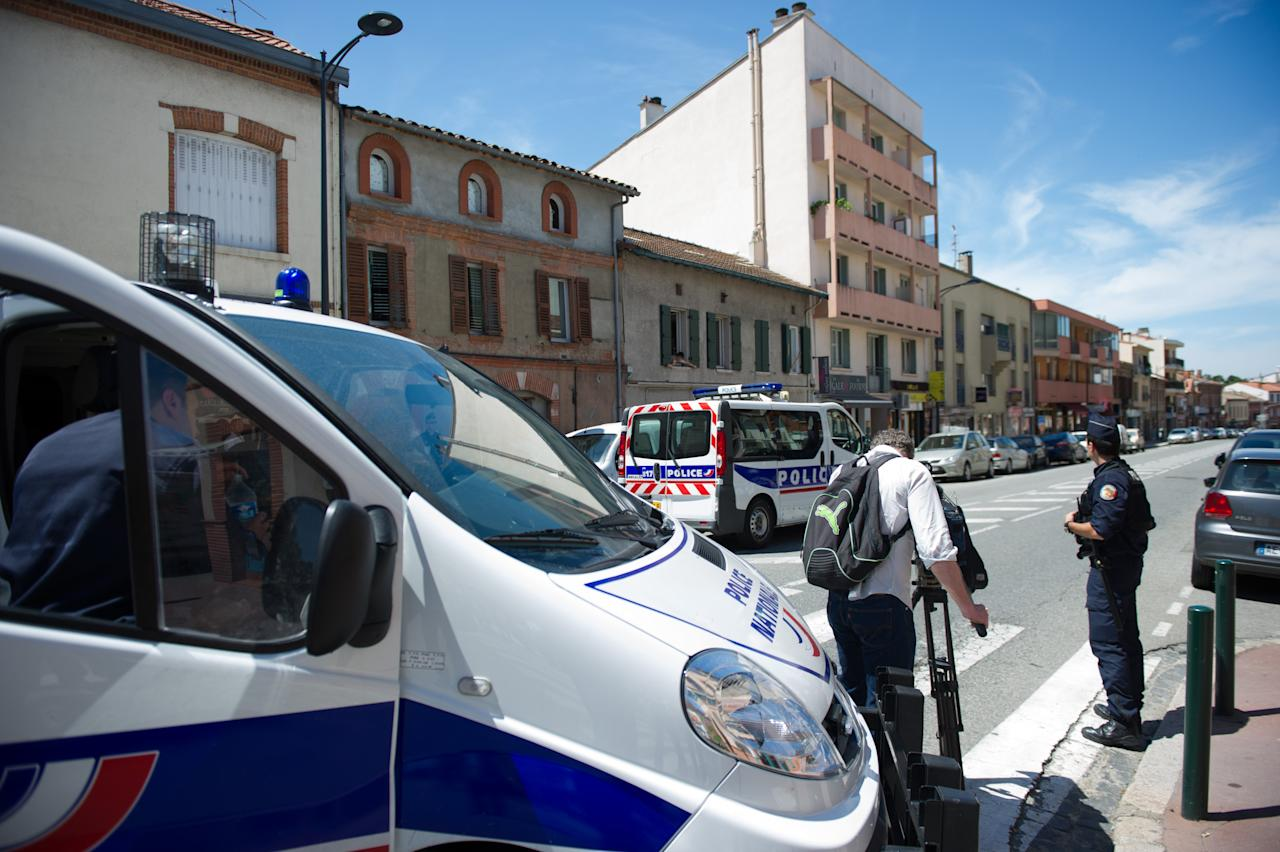 A police officers stands near a cameraman near where a man took hostages in a bank in the southern French city of Toulouse and fired a shot, police said, Wednesday, June 20, 2012. French television reported that he claimed allegiance to the al-Qaida terrorist group.(AP Photo/Bruno Martin)
