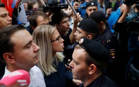 Ivan Zhdanov and Lyubov Sobol, allies of opposition leader Alexei Navalny whose candidacies have been rejected, confront police outside the electoral commission on Sunday - Credit: Pavel Golovkin/AP