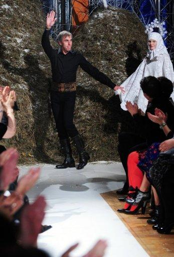 "French designer Philippe Guilet acknowledges the audience after a fashion event called ""100%.RO"" held at the French embassy headquarters in Bucharest. Sheepskin skirts and delicate bead embroidery shone on the catwalk in a one-of-a-kind ethnic fashion show blending the skills of the French designer and centuries-old Romanian handicraft"