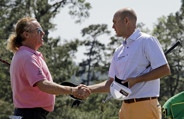 Miguel Angel Jimenez, of Spain, shakes hands with Bill Haas, right, on the 18th green following their first round of the Masters golf tournament Thursday, April 10, 2014, in Augusta, Ga. (AP Photo/David J. Phillip)