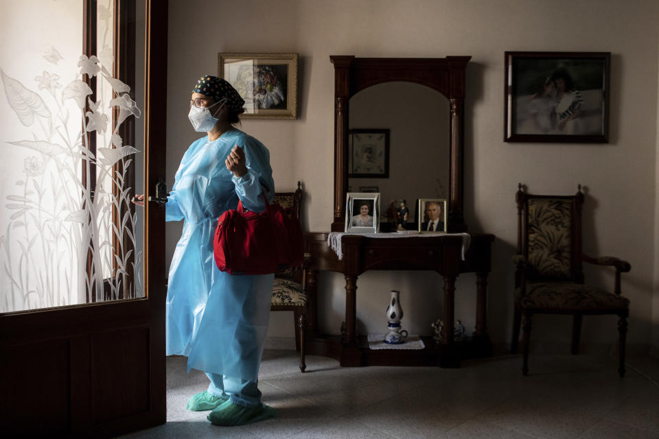 Nurse Pilar Rodríguez leaves the house of her patient Antonia Crespi, 93, in the town of Sa Pobla on the Spanish Balearic Island of Mallorca, Spain, Friday, April 30, 2021. (AP Photo/Francisco Ubilla)