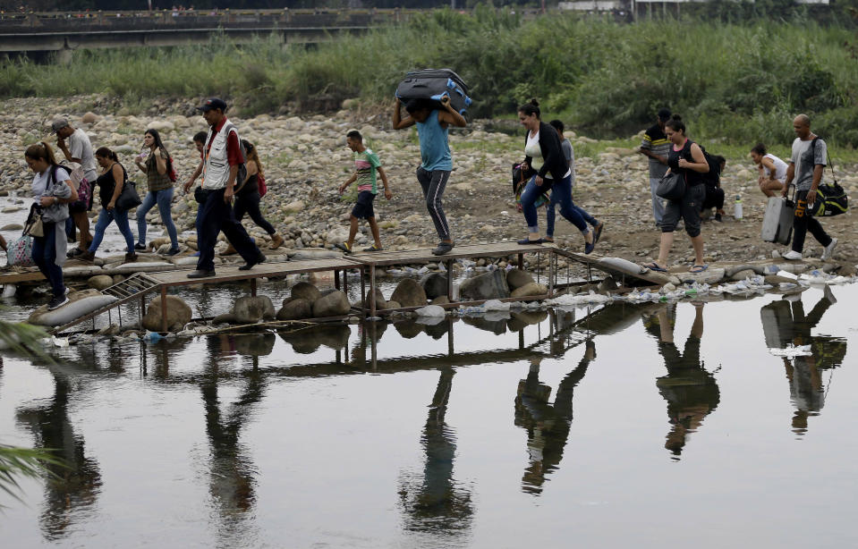 """FILE - In this April 14, 2019 file photo, Venezuelans cross illegally into Colombia near the Simon Bolivar International Bridge, top, which is partially closed by Venezuelan authorities who are only permitting students, seniors and the sick to cross, seen from La Parada near Cucuta, Colombia. President Nicolas Maduro's government has described the migrant exodus from Venezuela as """"normal"""" and denied there is a humanitarian crisis, despite considerable evidence that there is. (AP Photo/Fernando Vergara, File)"""