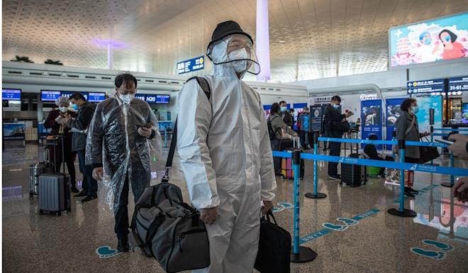 Passengers line up for one of the 100 commercial flights out of Wuhan on Wednesday. Photo: EPA-EFE