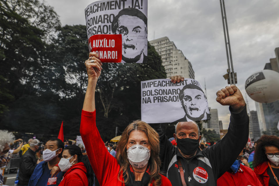 """Demonstrators hold signs that read in Portuguese; """"Impeachment now! Bolsonaro in prison"""" during a protest against Brazilian President Jair Bolsonaro and his handling of the COVID-19 pandemic, on Paulista Avenue in Sao Paulo, Brazil, Saturday, June 19, 2021. Brazil's COVID-19 death toll is expected to surpass the milestone of 500,000 deaths on Saturday night. (AP Photo/Marcelo Chello)"""