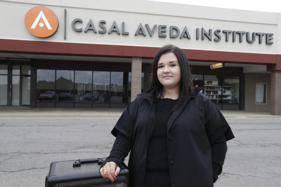 In this Friday, May 8, 2020 photo, Christa Schall poses outside her cosmetology school, Casal Aveda Institute, in Austintown, Ohio. More than 8 million students in the U.S. are enrolled in technical colleges, seeking certification in skilled trades like welding, phlebotomy and cosmetology. But unlike students at traditional colleges, their learning can't easily translate into Zoom courses, they learn through hands-on demonstrations. Now, many are eager to get back into the classroom, and some are reeling because they won't get to graduate on time. (AP Photo/Tony Dejak)