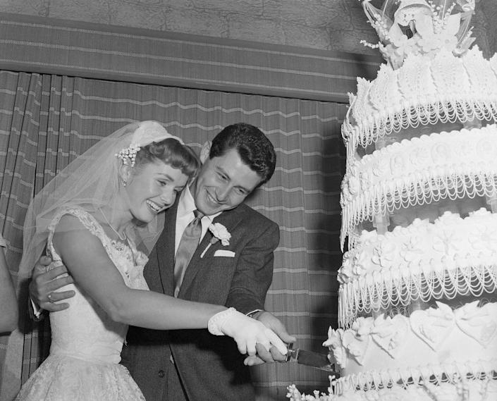 <p>Hollywood's girl next door looked radiant in the full-skirt lace bridal gown when she wed Eddie Fisher. The couple cut into their enormous tiered wedding cake at their reception in Liberty, New York. </p>