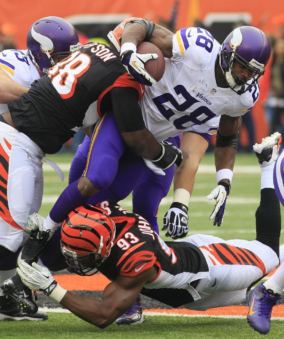 Minnesota Vikings running back Adrian Peterson (28) is tackled by Cincinnati Bengals defensive tackle Brandon Thompson (98) and defensive end Michael Johnson (93) in the first half of an NFL football game on Sunday, Dec. 22, 2013, in Cincinnati. (AP Photo/Tom Uhlman)