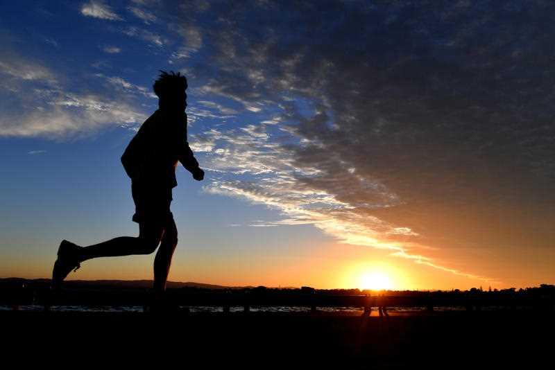 A man is seen jogging as the sun sets at Woody Point in Redcliffe, Queensland.