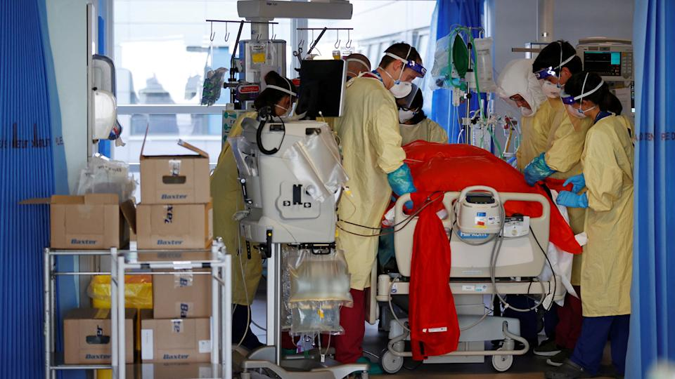 Firefighters Dan Joslin (C) and Matt Smither (2R) help prone a Covid-19 patient as they work alongside critical care nurses in the Intensive Care Unit (ICU) at Queen Alexandra Hospital in Portsmouth, southern England on March 23, 2021. (Adrian Dennis/AFP via Getty Images)
