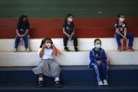 First-grade students wear masks and socially distance in the gym during class at San Juan Bautista technical school in Lambare, Paraguay, Wednesday, Feb. 17, 2021. Some private primary schools opened in-person classes this week with strict health security protocols amid the COVID-19 pandemic. (AP Photo/Jorge Saenz)