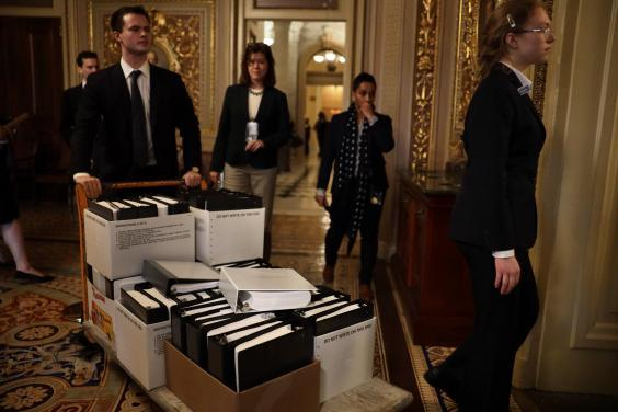 Stacks of legal papers are wheeled in ahead of the hearing (Getty)