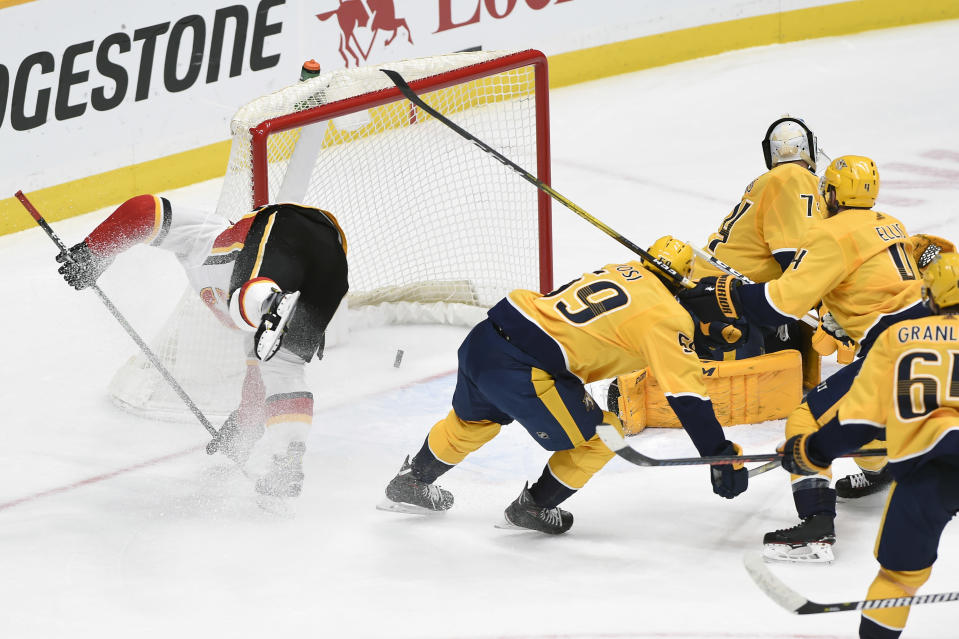 Calgary Flames center Mikael Backlund, left, of Sweden, moves toward the net after a go-ahead goal in the third period by teammate left wing Andrew Mangiapane (88) in an NHL hockey game against the Nashville Predators, Thursday, Feb. 27, 2020, in Nashville, Tenn. (AP Photo/Mark Zaleski)