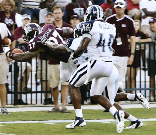 Mississippi State's LaDarius Perkins, left dives for the goal line in front of Jackson State defenders Mike Hill, center, and Todd Wilcher (40) during the first half of their NCAA college football game in Starkville, Miss., Saturday, Sept. 1, 2012. (AP Photo/Jim Lytle)