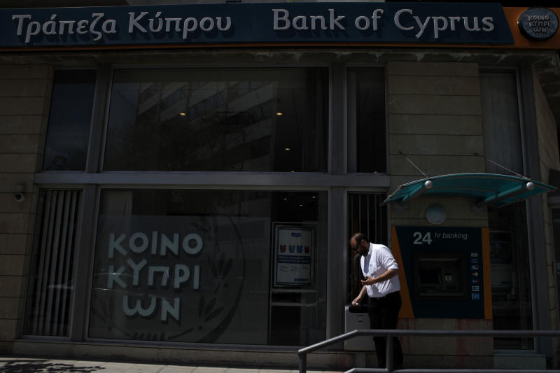 """A man leaves the the ATM machines of a branch of bank of Cyprus in central capital Nicosia, Cyprus, Friday, April 12, 2013. President Nicos Anastasiades said that he will dispatch letters to EU Commission President Jose Manuel Barosso and EU Council chief Herman Van Rompuy telling them of the """"need for a change of EU policy"""" toward Cyprus by offering additional assistance. (AP Photo/Petros Karadjias)"""