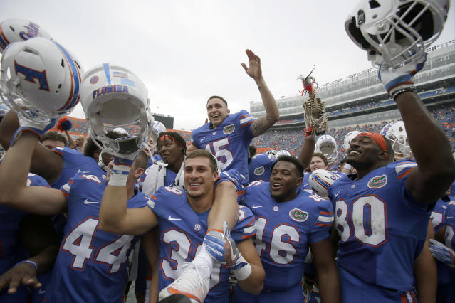 Eddy Pineiro (15) sits on the shoulders of his Florida teammates as they celebrate after defeating South Carolina in 2016. (AP)