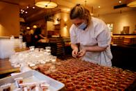 <p>A member of staff prepares packaged meals for the Luca at Home 'Valentines Menu for 2' at Luca restaurant in central London on February 12, 2021, as restaurants remain restricted to home deliveries during the nation-wide coronavirus Covid-19 lockdown (Photo by Tolga Akmen / AFP) (Photo by TOLGA AKMEN/AFP via Getty Images)</p>