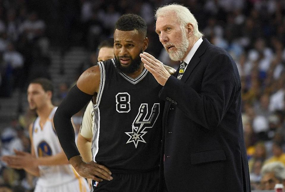 Head coach Gregg Popovich of the San Antonio Spurs talks with Patty Mills, who tallied a season-best 19 points against the Boston Celtics (AFP Photo/Thearon W. Henderson)