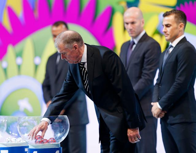 Former soccer great and World Cup winner Geoff Hurst of England takes a lot from a bowl during the draw ceremony for the 2014 soccer World Cup in Costa do Sauipe near Salvador, Brazil, Friday, Dec. 6, 2013. (AP Photo/Andre Penner)