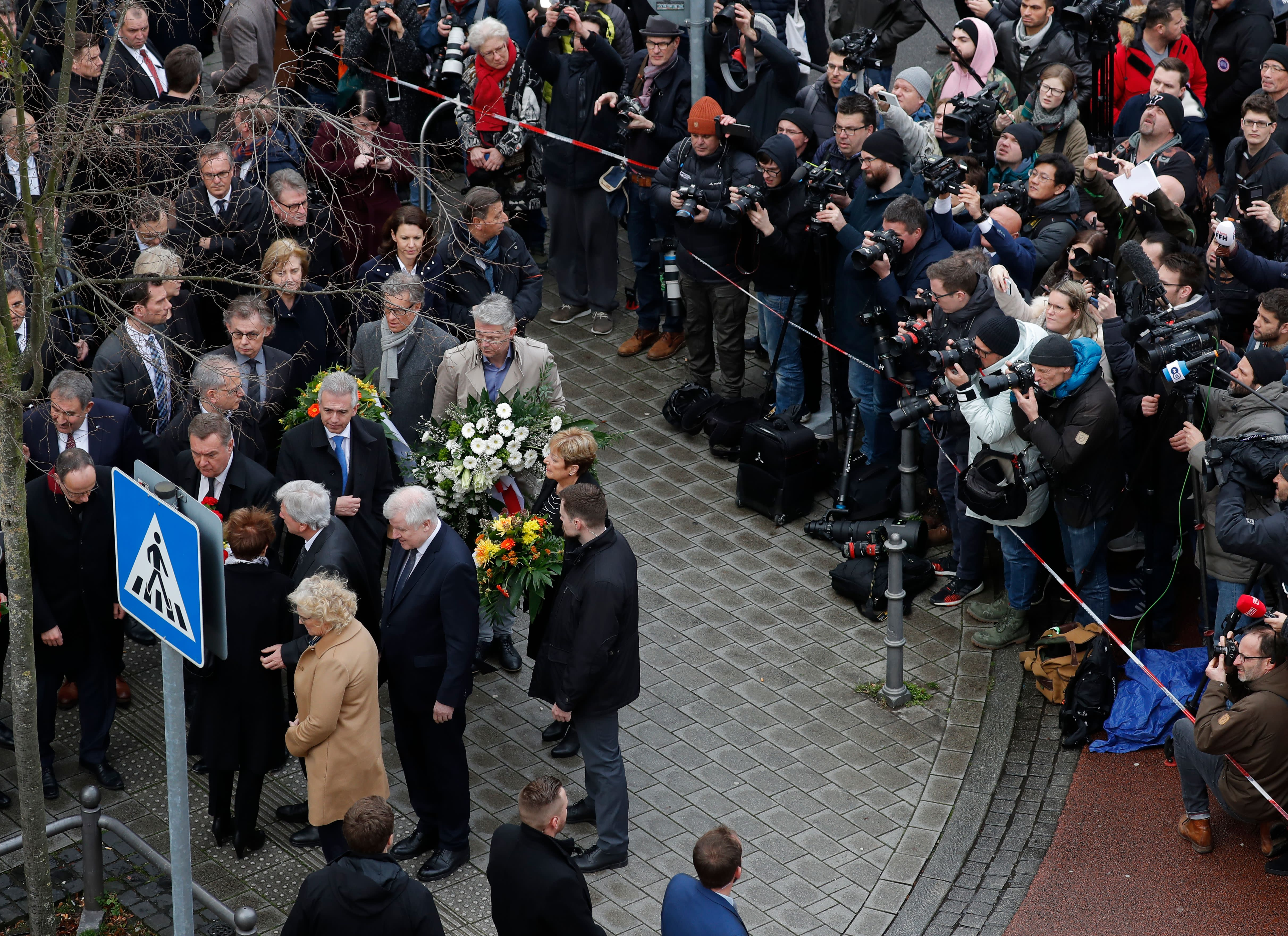 (L-R) German Justice Minister Christine Lambrecht, German Interior Minister Horst Seehofer, Hesse's State Premier Volker Bouffier and Hesse state Interior Minister Peter Beuth arrive to lay flowers in the area of the bar targeted in a shooting at the Heumarkt in the centre of Hanau, near Frankfurt am Main, western Germany, on February 20, 2020, after at least nine people were killed in two shootings late on February 19, 2020. - The suspect in two shootings in Germany that killed at least nine people was found dead at home, police said on February 20, 2020. At least nine people were killed in two shootings late on February 19 in Hanau, near the German city of Frankfurt. (Photo by Odd ANDERSEN / AFP) (Photo by ODD ANDERSEN/AFP via Getty Images)