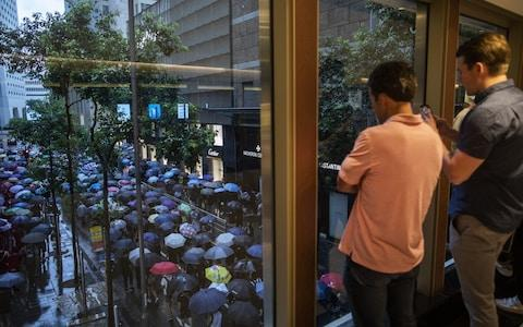 People look out from a pedestrian footbridge while demonstrators march along a road as rain falls during a protest in the Central district of Hong Kong - Credit: Justin Chin/Bloomberg