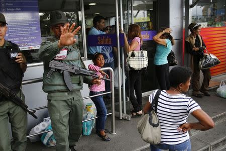 National guards stand at a supermarket entrance as people line up outside in Caracas January 19, 2015. REUTERS/Jorge Silva