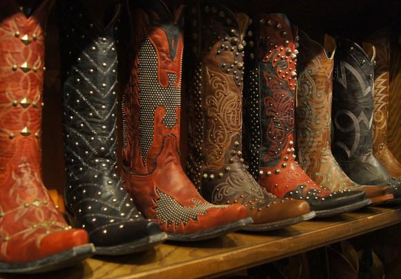 Ornate cowboy boots lined up on a wooden shelf