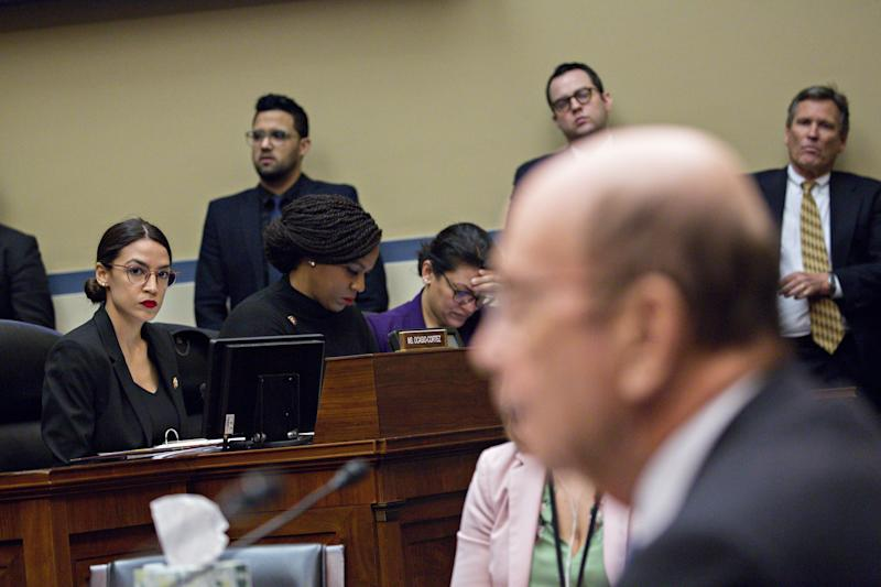 Representative Alexandria Ocasio-Cortez, a Democrat from New York, left, listens during a House Oversight Committee hearing with Wilbur Ross, U.S. commerce secretary, right, in Washington, D.C., U.S., on Thursday, March 14, 2019. A main topic of the hearing is to be allegations by committee Democrats that Ross has given misleading testimony on multiple occasions to Congress about the citizenship question to the 2020 Census. Photographer: Andrew Harrer/Bloomberg via Getty Images