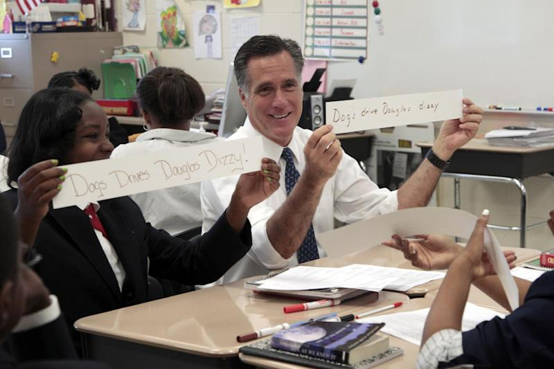 Republican presidential candidate, former Massachusetts Gov. Mitt Romney, and Salina Beattie display class work they did together in the 6th grade language arts class during Romney's tour of the Universal Bluford Charter School, Thursday, May 24, 2012, in Philadelphia.  (AP Photo/Mary Altaffer)