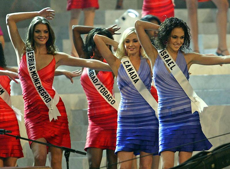 QUITO, ECUADOR: Miss Serbia&Montenegro Dragana Dujovic, Miss Canada Vennesa Fisher and Miss Israel Gal Gadot dance on the stage during the first official presentation with the panel of judges in Quito, 27 May 2004. The Miss Universe 2004 contest will take place on 01 June. AFP PHOTO/Martin BERNETTI (Photo credit should read MARTIN BERNETTI/AFP via Getty Images)