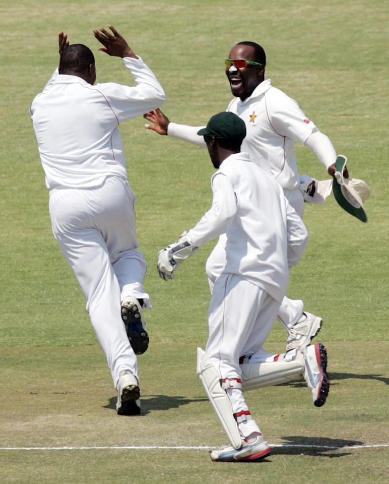 Zimbabwe's fielder Hamilton Masakadza celebrates a wicket with his teammates on the fifth day of the second test match between Pakistan and Zimbabwe at the Harare Sports Club on September 14, 2013. AFP PHOTO / JEKESAI NJIKIZANA        (Photo credit should read JEKESAI NJIKIZANA/AFP/Getty Images)