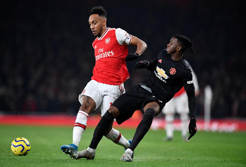 Arsenal's Pierre-Emerick Aubameyang (left) in action with Manchester United's Aaron Wan-Bissaka.