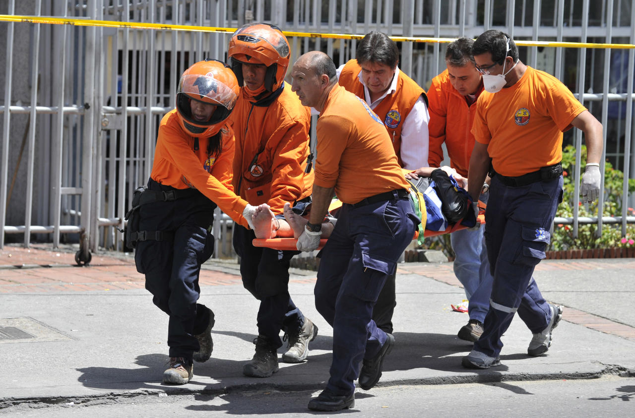 Rescue workers carry an injured person after a bomb explosion in Bogota, Colombia, Tuesday, May 15, 2012. A bomb targeting former Colombian interior minister Fernando Londono killed two of his bodyguards and injured at least 31 others in the heart of Bogota's uptown commercial district, authorities said. (AP Photo/Carlos Julio Martinez)