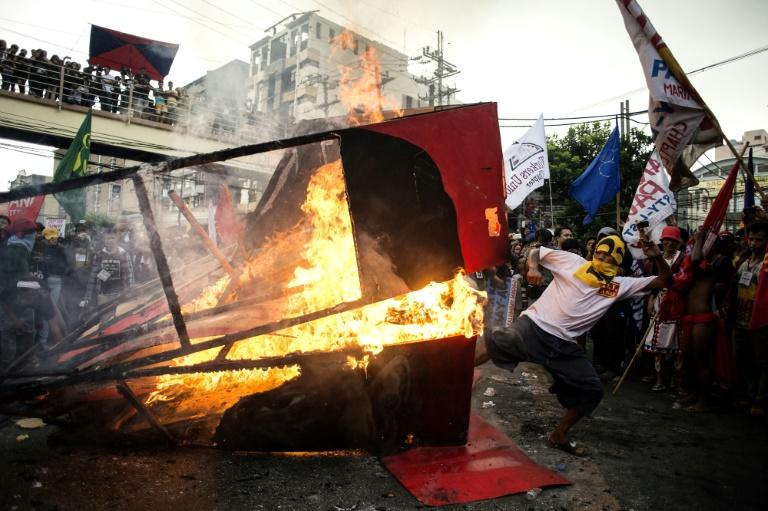 Activists burn an effigy during a protest against Philippine President Rodrigo Duterte near the Malacanang palace in Manila