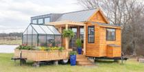 """<p>With an attachable greenhouse and porch, the Elsa by Olive Nest Tiny Homes proves that you can still have it all in a small space.</p><p><a class=""""link rapid-noclick-resp"""" href=""""https://tinyhouselistings.com/listings/taylors-sc-12-the-elsa/"""" rel=""""nofollow noopener"""" target=""""_blank"""" data-ylk=""""slk:SHOP NOW"""">SHOP NOW</a> <a class=""""link rapid-noclick-resp"""" href=""""https://www.countryliving.com/home-design/house-tours/news/a45229/greenhouse-tiny-home/"""" rel=""""nofollow noopener"""" target=""""_blank"""" data-ylk=""""slk:SEE INSIDE"""">SEE INSIDE</a> </p>"""