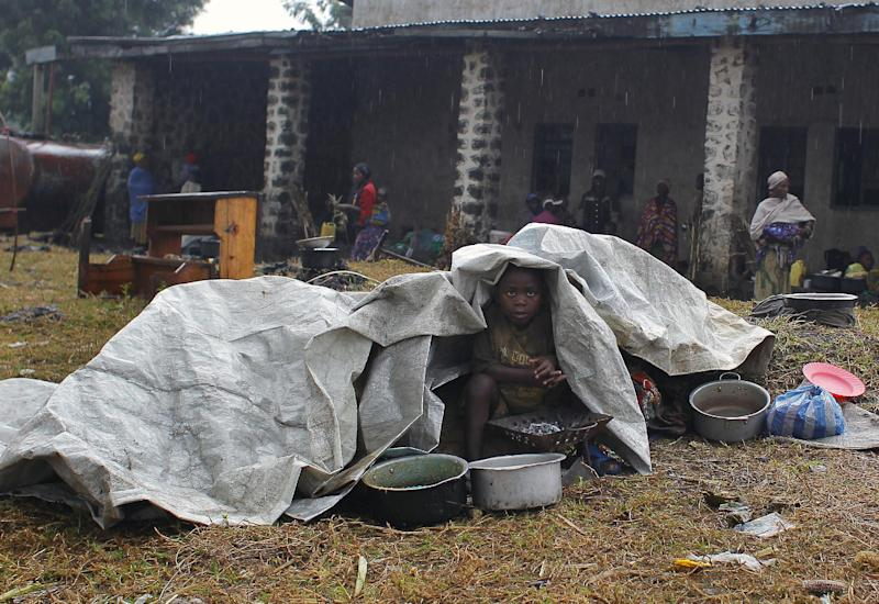 An internally displaced Congolese child shelters himself and his siblings from the rain under a plastic sheet as they wait for aid to be distributed in Kibati, north of Goma, eastern Congo, Wednesday Aug. 8, 2012. Drenching rain punctuated by frightening bursts of thunder and forked lightning add to the misery of some of the 280,000 refugees from Congo's eastern rebellion, whose plight is highlighted by a visit from the U.N. humanitarian chief Baroness Valerie Amos. (AP Photo/Jerome Delay)