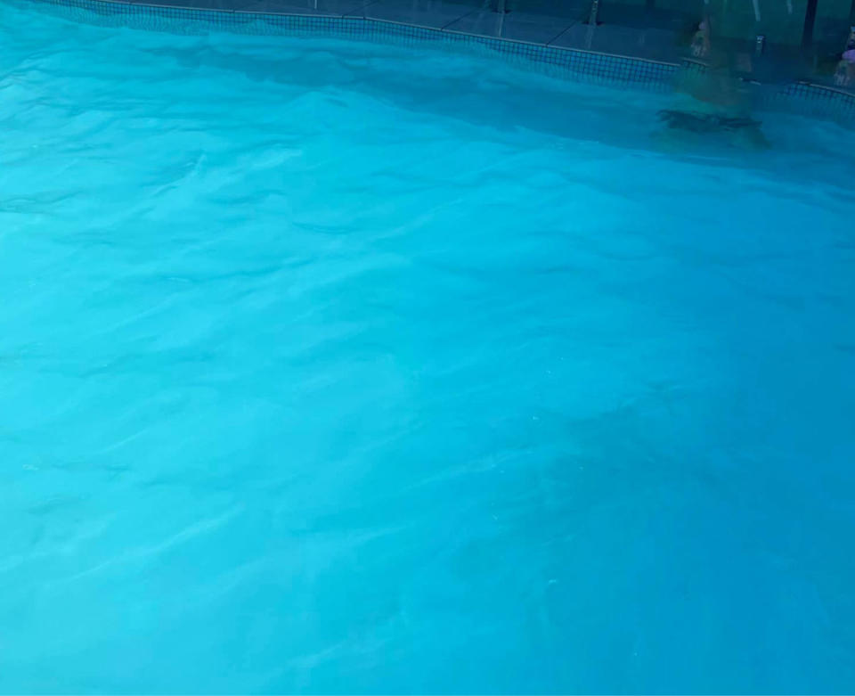 A child at the bottom of a backyard swimming pool is barely visible at the surface.