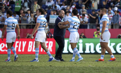 Argentina coach Mario Ledesma shakes hands with Matas Moroni as the players leave the field following their Rugby World Cup Pool C game at Kumagaya Rugby Stadium between Argentina and the United States in Kumagaya City, Japan, Wednesday, Oct. 9, 2019. (AP Photo/Eugene Hoshiko)