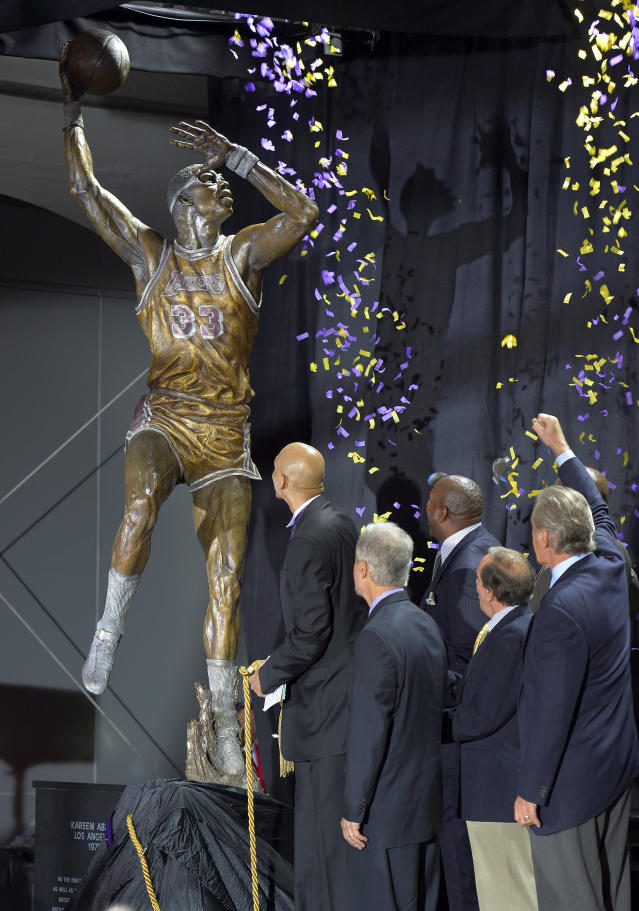 """Former Los Angeles Lakers center Kareem Abdul-Jabbar, left, unveils a statue of himself in front of Staples Center as Richard Lapchik, second from left, Earvin """"Magic"""" Johnson, third from right, Eddie Doucette, second from right, and Pat Riley look on, Friday, Nov. 16, 2012, in Los Angeles. (AP Photo/Mark J. Terrill)"""