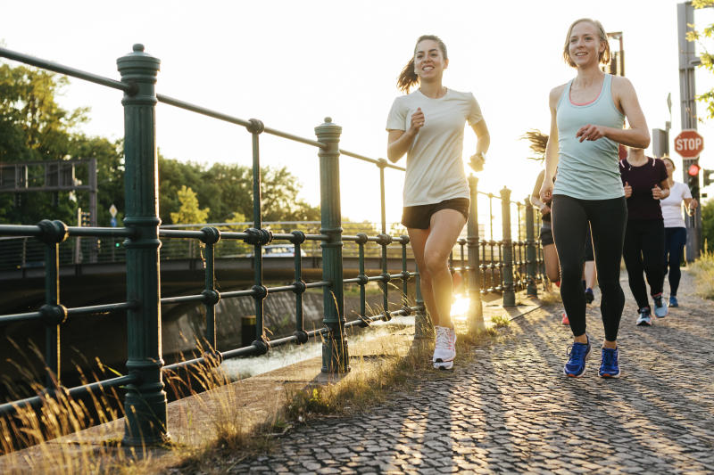 A group of women keeping fit by running in the city together alongside a canal.