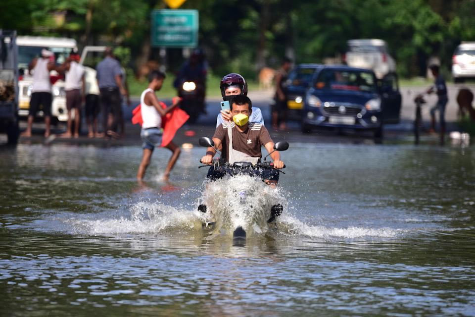 People cross flooded national highway 37 at Kaziranga in Nagaon District of Assam. (Photo credit should read Anuwar Ali Hazarika/Barcroft Media via Getty Images)
