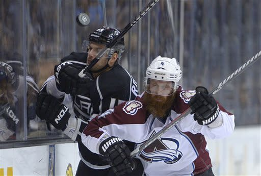 Los Angeles Kings center Brad Richardson, left, and Colorado Avalanche defenseman Greg Zanon battle for the puck during the second period of their NHL hockey game, Thursday, April 11, 2013, in Los Angeles. (AP Photo/Mark J. Terrill)